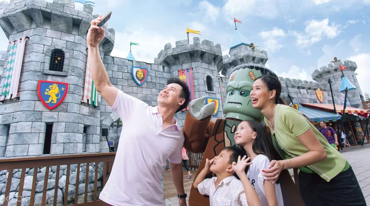 a family taking a selfie beside a LEGOLAND® castle
